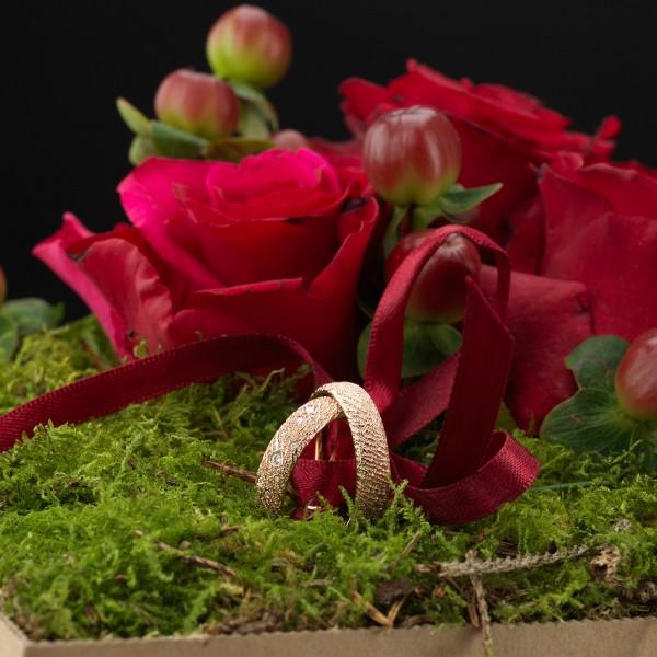 Eheringe elegant überreichen: Die Loving Nature blühauf-Blumenbox zaubert ein Lächeln auf ihre Lippen.